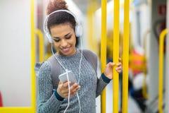 Ung kvinna som använder mobiltelefonen på gångtunnelen Arkivfoton