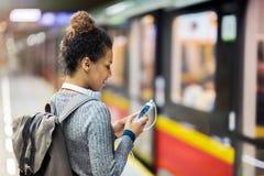 Ung kvinna som använder mobiltelefonen på gångtunnelen Fotografering för Bildbyråer