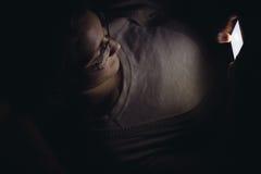 Ung kvinna som använder mobiltelefonen på natten i mörker Royaltyfri Bild