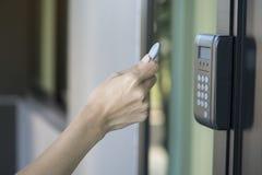 Ung kvinna som använder RFID-etikettstangent för att öppna dörren arkivbilder