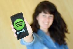 Ung kvinna som använder service SPOTIFY för populär musik arkivbilder