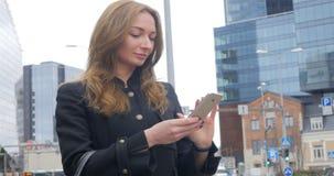 Ung kvinna som använder smartphonen arkivfilmer