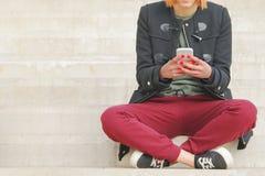Ung kvinna som använder smartphonen Arkivbild