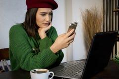 Ung kvinna som använder smartphonen i ett kafé med en bärbar dator arkivbild