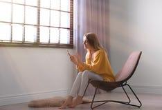 Ung kvinna som använder smartphonen nära fönster med rullgardiner royaltyfri fotografi