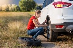 Ung kvinna som använder stålar för att lyfta hennes bil med det plana gummihjulet och för att skruva av hjulmuttrar Fotografering för Bildbyråer