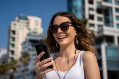 Ung kvinna som använder telefonen med hörlurar med mikrofon Stadshorisont i bakgrund royaltyfri fotografi