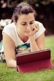 Ung kvinna som använder utomhus- lägga för tablet på gräs royaltyfria bilder