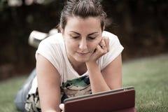 Ung kvinna som använder utomhus- lägga för tablet på gräs royaltyfri foto