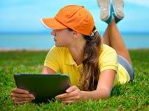Ung kvinna som använder utomhus- lägga för tablet på gräs Arkivfoton