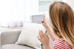 Ung kvinna som använder video pratstund på smartphonen i rum, closeup Utrymme f?r design arkivfoto