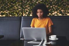 Ung kvinna som anv?nder b?rbara datorn i kaf? arkivbilder