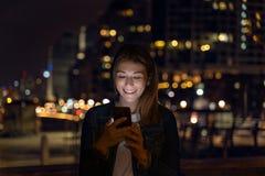 Ung kvinna som anv?nder hennes smartphone under natten stadsljus som bakgrund royaltyfri foto