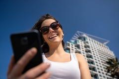Ung kvinna som anv?nder telefonen Stadshorisont i bakgrund royaltyfria bilder