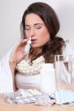 Ung kvinna som använder nasal sprej i hennes vardagsrum Arkivbild