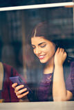 Ung kvinna som använder teknologi i kafé Arkivfoto