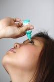 Ung kvinna som applicerar eyedrops. Arkivfoto