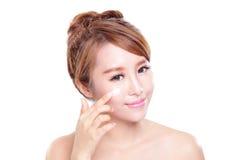 Ung kvinna som applicerar fuktighetsbevarande hudkrämkräm på framsida arkivfoto