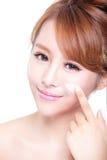 Ung kvinna som applicerar fuktighetsbevarande hudkrämkräm på framsida Royaltyfria Foton
