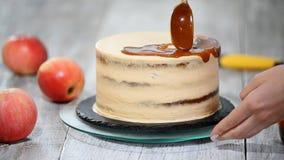 Ung kvinna som applicerar karamellsås på den läckra hemlagade kakan på tabellen Läcker kaka med äpplet och piskad kräm lager videofilmer