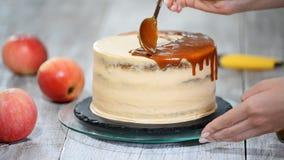 Ung kvinna som applicerar karamellsås på den läckra hemlagade kakan på tabellen Läcker kaka med äpplet och piskad kräm arkivfilmer