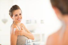 Ung kvinna som applicerar kräm i badrum Royaltyfri Fotografi