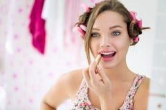 Ung kvinna som applicerar läppstift i badrum arkivfoto