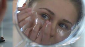 Ung kvinna som applicerar lappar under ögon, lyftande effekt, hem- brunnsortuppfriskning stock video