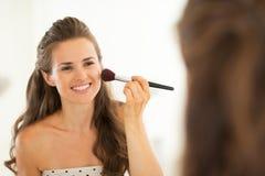 Ung kvinna som applicerar makeup i badrum Arkivfoto