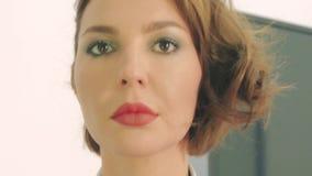 Ung kvinna som applicerar makeup i spegelnärbilden lager videofilmer