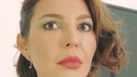Ung kvinna som applicerar makeup i spegelnärbilden stock video