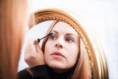 Ung kvinna som applicerar mascara Royaltyfri Bild