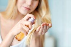 Ung kvinna som applicerar olja på hennes hår, Arkivbild
