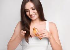 Ung kvinna som applicerar olja på hennes hår arkivfoto