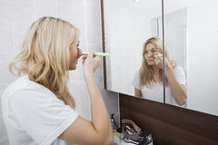 Ung kvinna som applicerar rodnad, medan se spegeln i badrum Arkivfoto