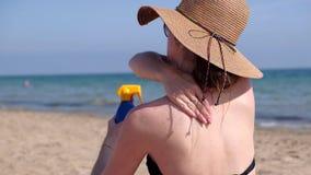 Ung kvinna som applicerar sunscreen för att flå på stranden arkivfilmer