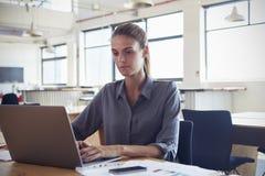 Ung kvinna som arbetar i ett kontor genom att använda en bärbar datordator arkivfoto
