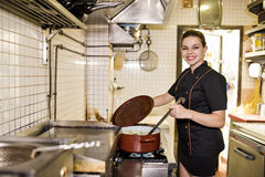Ung kvinna som arbetar i gammal kökmatlagning Arkivfoto