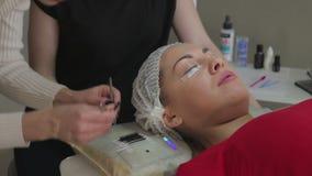 ung kvinna som arbetar på ögonfransförlängningar lager videofilmer