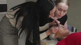ung kvinna som arbetar på ögonfransförlängningar stock video