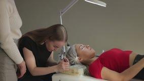 ung kvinna som arbetar på ögonfransförlängningar arkivfilmer