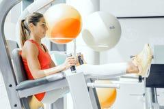 Ung kvinna som arbetar på abs i en idrottshall Royaltyfria Bilder