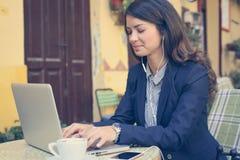 Ung kvinna som arbetar på bärbara datorn, lyssnande musik royaltyfria bilder