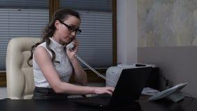 Ung kvinna som arbetar på bärbara datorn och talar på telefonen lager videofilmer