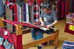 Ung kvinna som arbetar på en vävstol royaltyfri foto