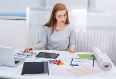Ung kvinna som arbetar på kontorsskrivbordet arkivbild