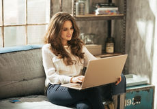 Ung kvinna som arbetar på bärbara datorn i vindlägenhet Royaltyfria Foton