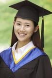 Ung kvinna som avlägger examen från universitetet, närbildlodlinjestående Arkivbild
