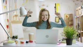 Ung kvinna som avslutar hennes arbete på bärbara datorn och är lycklig om den arkivfilmer