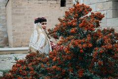 Ung kvinna som bär Azerbajdzjan den traditionella klänningen som utomhus poserar royaltyfri bild